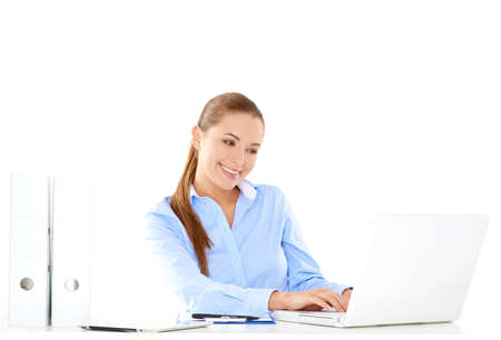 inundated: Smiling businesswoman sitting at her desk working on a laptop computer against a white background