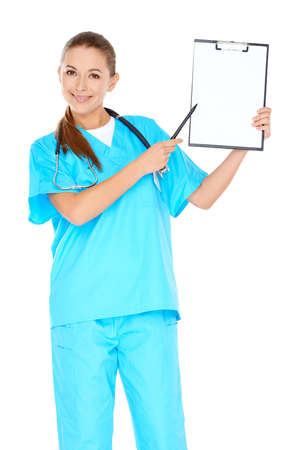 phisician: Smiling attractive young nurse or doctor in green scrubs holding up a blank clipboard in her hand and pointing towards it with a pen  isolated on white Stock Photo