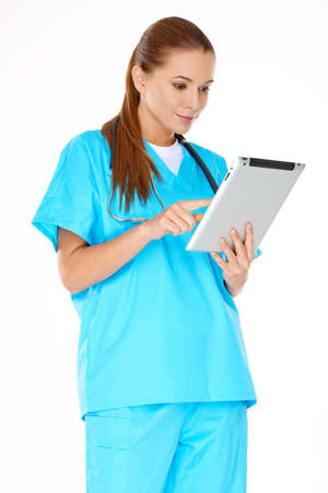 phisician: Dedicated young female nurse or doctor in green scrubs standing checking information on a handheld tablet computer  isolated on white