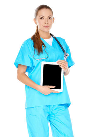 phisician: Attractive serious young female doctor or nurse in green scrubs with a tablet-pc or notebook displayed in her hands  screen visible to viewer Stock Photo