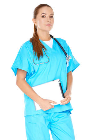 phisician: Attractive serious young female doctor or nurse in green scrubs with a tablet-pc or notebook displayed in her hands