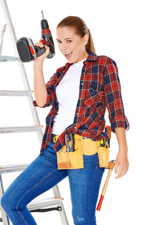 brandishing: Confident happy DIY handy woman standing on a stepladder with a tool belt round her waist brandishing an electric drill in the air