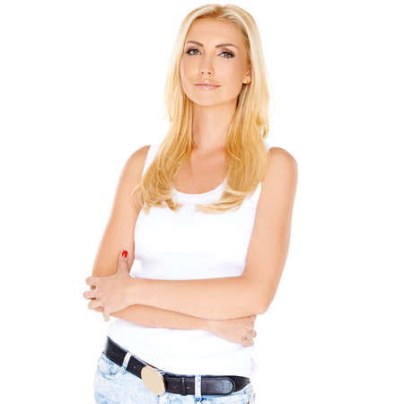 women jeans: Thoughtful casual young woman with long straight blond hair wearing trendy jeans standing looking pensively at the camera  isolated on white