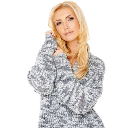 tilted: Portrait of a beautiful sensual blond woman cuddling into a warm knitted top standing with her head tilted looking at the camera with parted lips  isolated on white