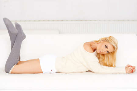 Elegant casual beautiful young woman with long blond hair relaxing lying on her stomach on a sofa with her feet in the air