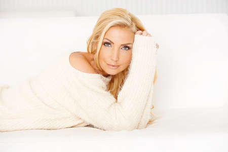 warm home: Attractive smiling young blond woman relaxing on a sofa lying on her stomach in a stylish white top