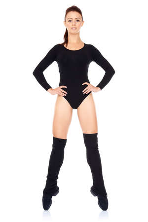 bodysuit: Confident athletic young woman working out in a leotard standing en pointe balanced on the tips of her toes with her hands on her hips isolated on white