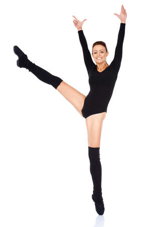bodysuit: Smiling happy beautiful ballet dancer working out in a black leotard holding a graceful en pointe pose on one foot with her arms raised and leg outstretched on a white reflective background