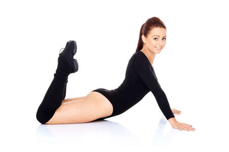 bodysuit: Fit sporty woman exercising and working out strengthening her abdominal muscles doing press ups and leg raisers over a white background