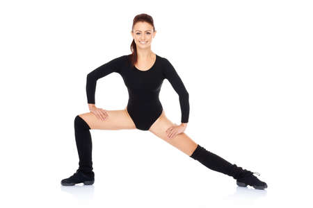 bodysuit: Fit healthy beautiful woman working out in a black leotard standing with outstretched legs and arms smiling at the camera  over a reflective white surface Stock Photo