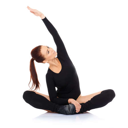 bodysuit: Athletic pretty young woman in a leotard working out sitting cross legged on the floor stretching her arm above her head  over white