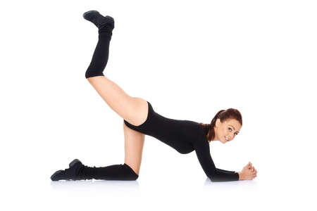 bodysuit: Fit young woman doing exercises working out kneeling on the floor with one leg raised in the air to strengthen and tone her muscles  on a white background Stock Photo