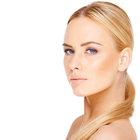 blonde blue eyes: Beautiful blond woman with blue eyes and her long hair neatly coiled over a bare shoulder looking at the camera isolated on white with copyspace