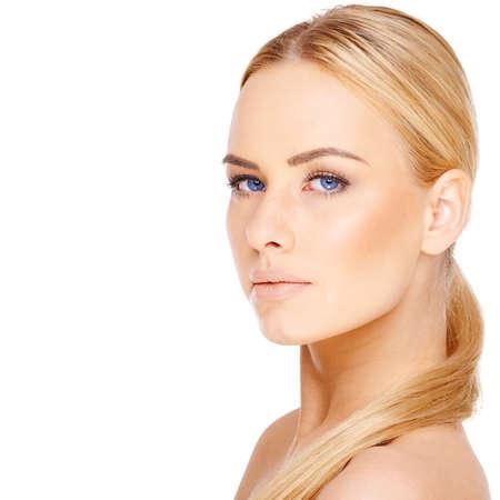 rubia ojos azules: Hermosa mujer rubia con ojos azules y su pelo largo bien enrollado sobre un hombro desnudo mirando a la c�mara aislada en blanco con copyspace