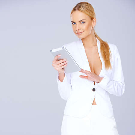 Elegant young blond woman in a sexy white suit standing texting on her mobile against a grey studio with copyspace photo