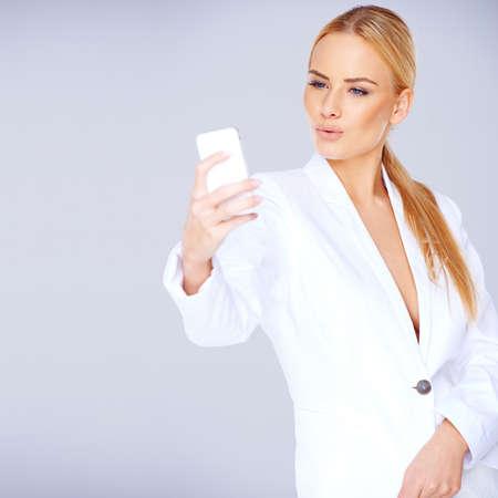 Elégante jeune femme blonde dans un costume blanc textos sexy debout sur son portable contre un studio gris avec atelier
