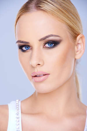 close up   head: Beautiful blue-eyed blond woman wearing dark eye makeup looking at the camera with parted lips  close up head portrait Stock Photo