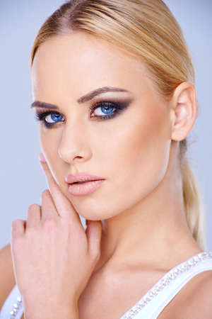 close up   head: Beautiful blue-eyed blond woman wearing dark eye makeup looking at the camera close up head portrait