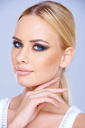 close up   head: Smiling blue-eyed blond woman wearing dark eye makeup looking at the camera close up head portrait