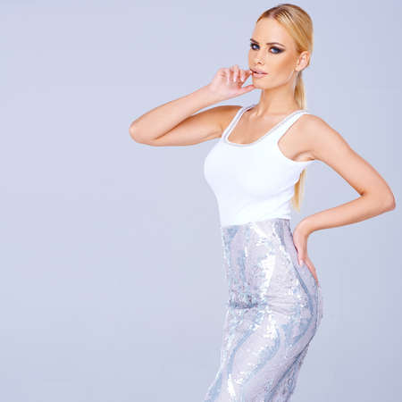 Tall elegant blond woman in a stylish slim line skirt standing posing with her hands on her hips on a blue-grey  photo