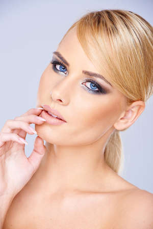 blonde  blue eyes: Beautiful dreamy young blond woman with downcast eyes wearing modern eye makeup  closeup face portrait on blue-grey
