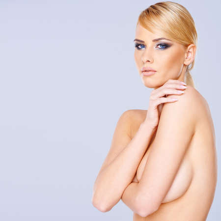 woman nude standing: Beautiful nude blond woman standing sideways concealing her breast with her arm looking at the camera on a grey with copyspace
