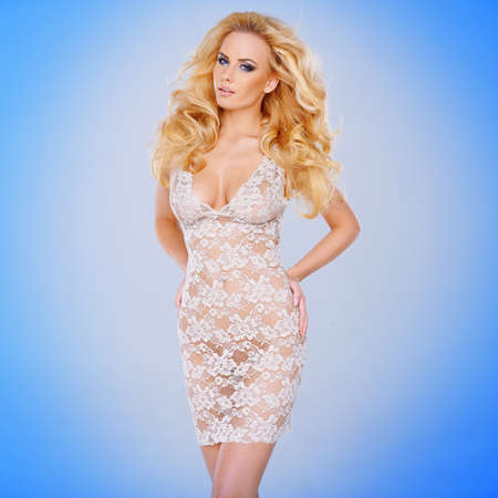 transparent dress: Glamorous young blond woman with a shapely figure in a sexy see-through lacy white dress against a blue  Stock Photo