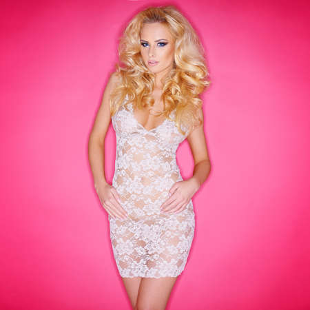 Sexy young blond woman with a shapely figure in a see-through lacy white dress against a pink  photo