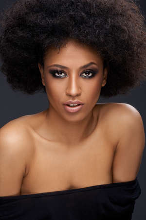 Beautiful glamorous Afro-American woman with a frizzy afro hairdo and bare shoulders photo