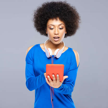interactivity: Beautiful young Afro-American woman selecting a tune on her storage device with a smile of anticipation