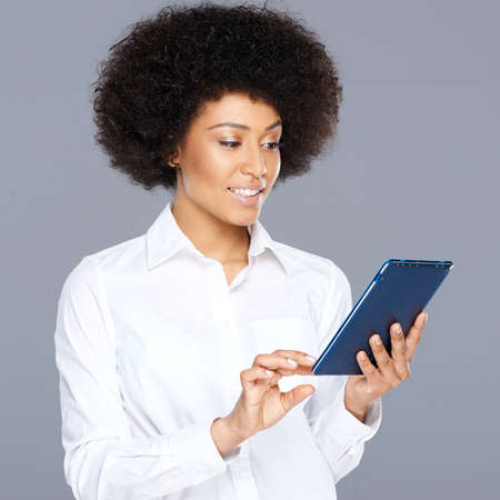Beautiful African American woman using her tablet surfing the internet and looking at information on the screen with a speculative disbelieving expression Banco de Imagens - 26466781