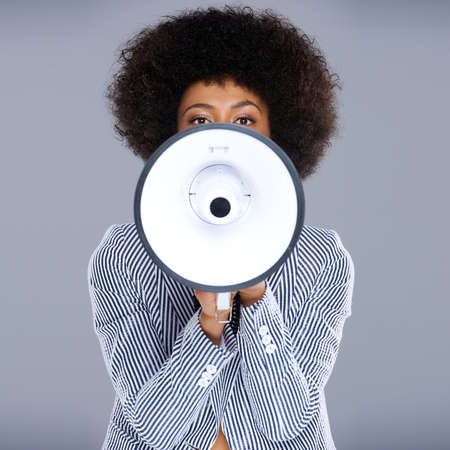 beautiful woman portrait: African American woman speaking into a megaphone making a public announcement with her face partially concealed, square format on grey