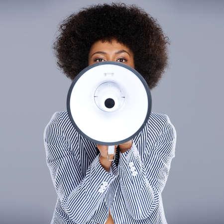 hablar en publico: Mujer afroamericana hablando en un megáfono de hacer un anuncio público con el rostro parcialmente oculto, formato cuadrado en gris Foto de archivo