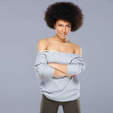 american sexy: Sexy beautiful African American woman with an afro hairstyle wearing a stylish off the shoulder top posing with folded arms, square format on grey Stock Photo