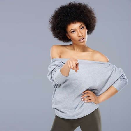 quizzical: Beautiful African American woman pointing at the camera with a quizzical expression and her hand on her hip, on grey Stock Photo