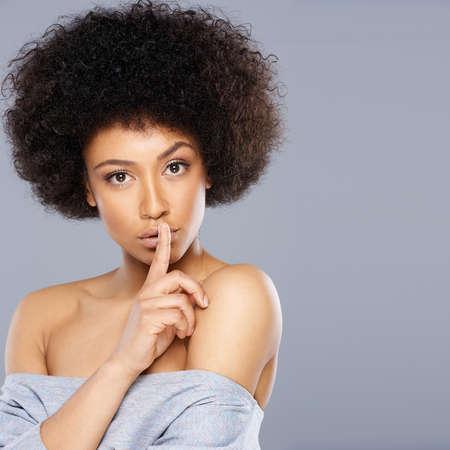 discreto: Hermosa mujer afroamericana con un gran peinado afro haciendo un gesto silenciar sosteniendo su dedo a sus labios mientras pide silencio, con copyspace