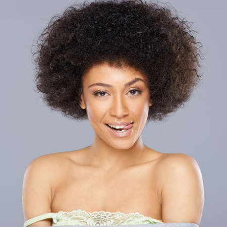 female tongue: Pretty African American woman with a lovely smile and a cute frizzy afro hairstyle standing with bare shoulders smiling at the camera Stock Photo