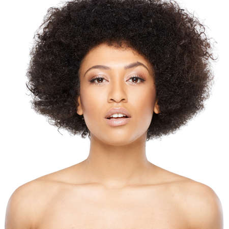 tilted: Beautiful serious young African American woman with bare shoulders looking at the camera with her head tilted and a serious expression, isolated on white Stock Photo