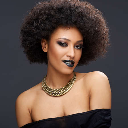 bare shoulders: Beautiful glamorous Afro-American woman with a frizzy afro hairdo and bare shoulders wearing a gold choker and stylish dark makeup