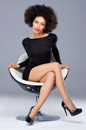 cocktaildress: Elegante mooie Afro-Amerikaanse vrouw in een zwarte cocktail jurk en hoge hielen zitten in een eigentijdse fauteuil op een grijze