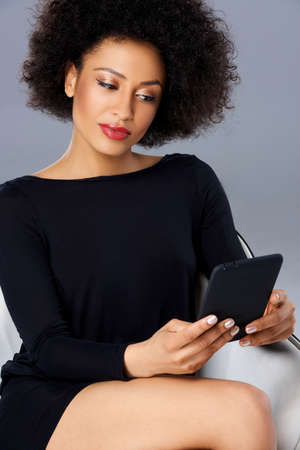 afro hairdo: Vivacious chic African American woman with a wild afro hairdo posing in a glamorous see through pink top with a tablet tucked into the waistband of her slacks smiling at the camera Stock Photo