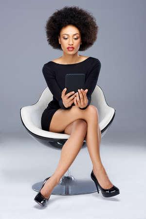 mujeres sentadas: Elegante glamorosa mujer afroamericana sentado en un vestido de cóctel negro y zapatos de tacón alto en un moderno sillón de diseño leyendo su Tablet PC Foto de archivo