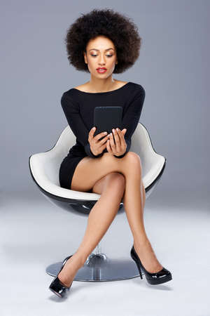 Elegant glamorous African American woman sitting in a black cocktail dress and high heels in a modern design armchair reading her tablet computer