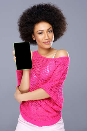 Smiling stylish sexy young African American woman with a tablet-pc holding it up to display the blank screen to the viewer photo