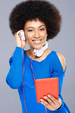 interactivity: Beautiful African American woman listening to music downloaded on her tablet computer holding one of the earphones to her ear while smiling happily at the camera