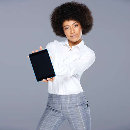 interactivity: Stylish trendy beautiful African American woman showing a tablet computer holding the blank screen towards the viewer