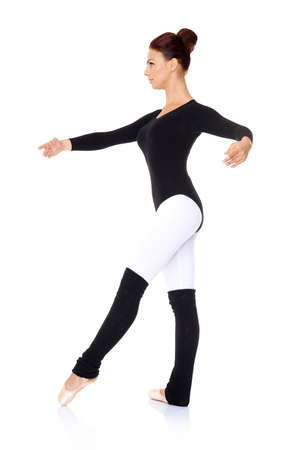 Beautiful female ballet dancer in a black leotard and leggings practising her steps and positions striking a graceful pose on a white  photo