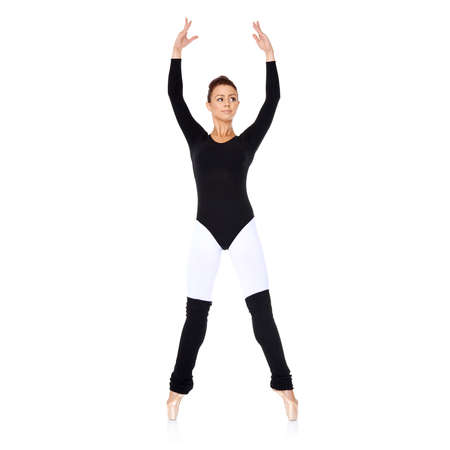 Beautiful graceful ballerina practicing her ballet in a black leotard with outstretched arms and leg over a reflective white  photo