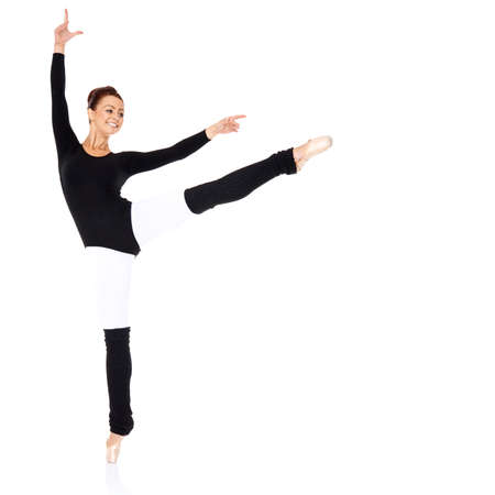 Graceful ballerina training in a black leotard and leggings practicing her ballet positions over a white  photo