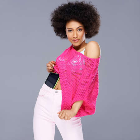 Vivacious chic African American woman with a wild afro hairdo posing in a glamorous see through pink top with a tablet tucked into the waistband of her slacks smiling at the camera photo